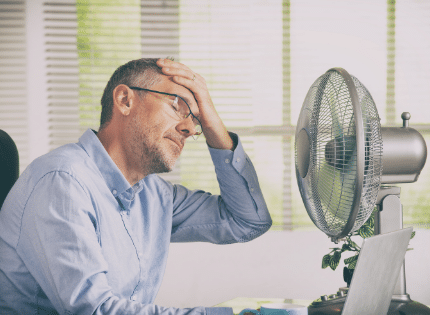 A man cooling off in front of the fan