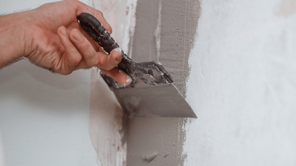 contractor sealing cracks on the wall