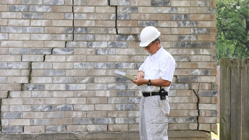 contractor with a white hat inspecting the home foundation