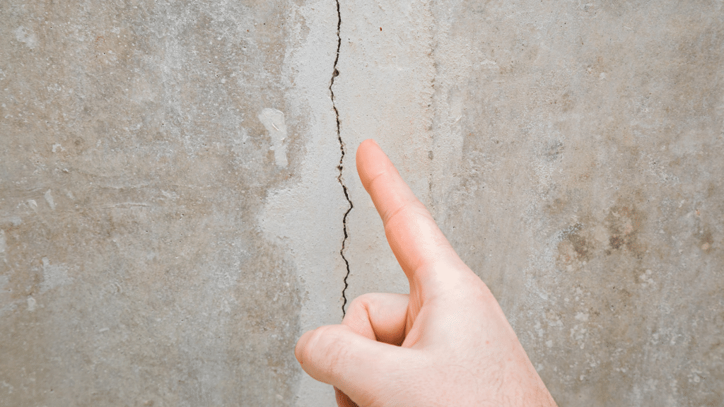 finger pointing at a vertical wall crack