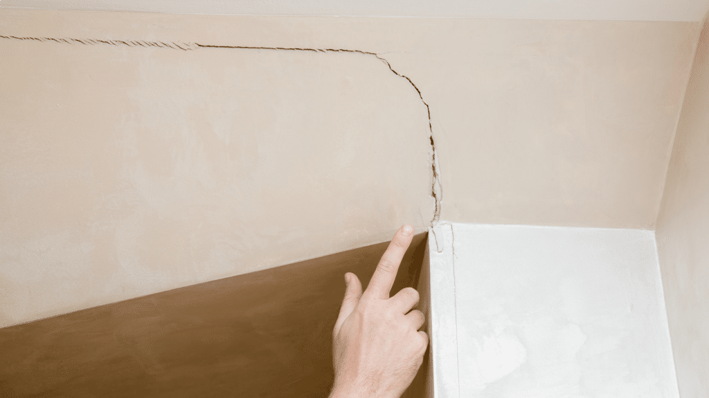 finger pointing at a wall crack
