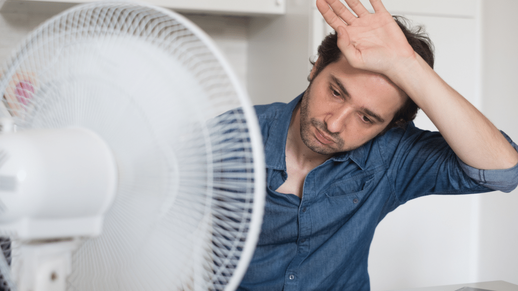 man cooling off in front of the fan