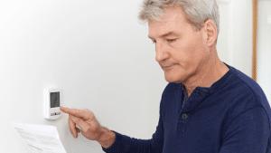 man in blue shirt looking at utility bills