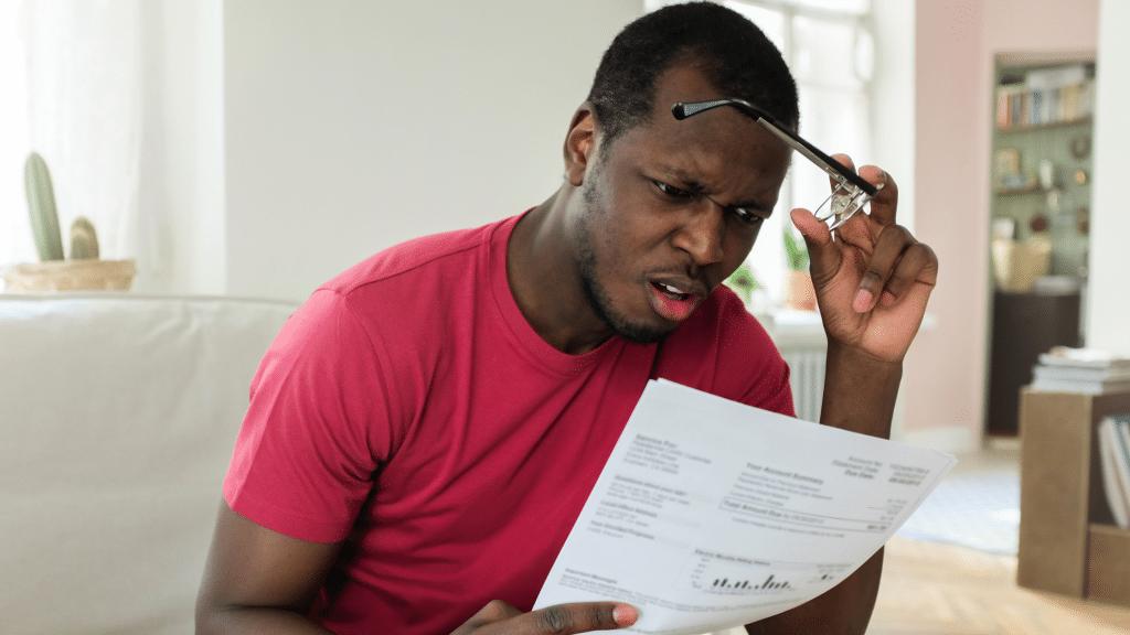 shocked man looking at bills