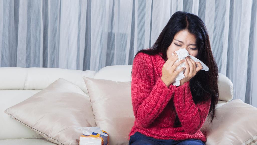 woman in pink sweater having allergy symptoms