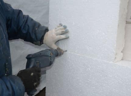 Attaching rigid foam insulation to a concrete wall