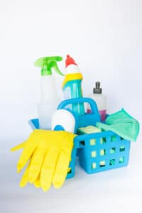 A basket of cleaning supplies with yellow rubber gloves